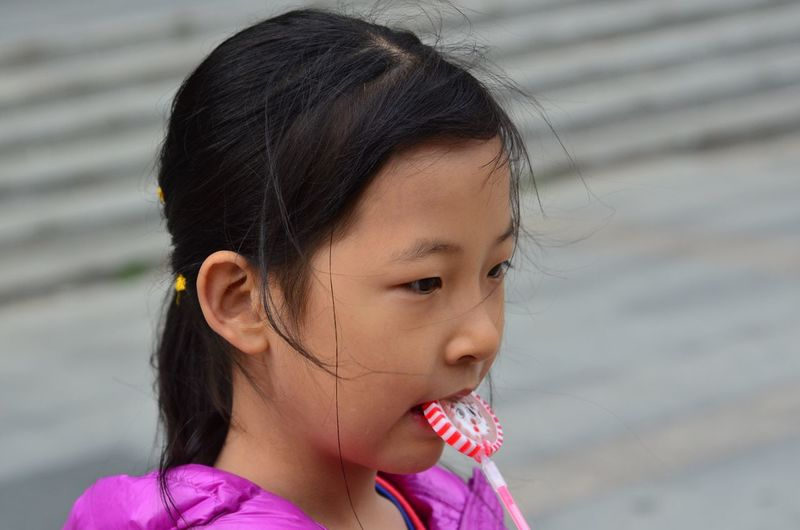 Close-up of girl eating candy