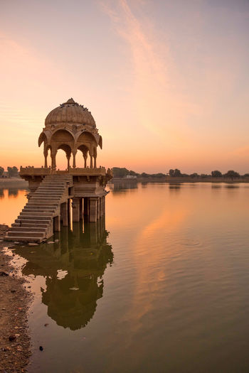 Sunrise over stone tower and historical building in Gadi Sagar lake, Jaisalmer, India. Ancient Civilization Architecture Building Exterior Built Structure Gadisagar Temple Gadisarlake History Jaisalmer Lake Nature No People Orange Color Outdoors Reflection Religion Scenics - Nature Sky Sunset The Past Tourism Travel Travel Destinations Water Waterfront