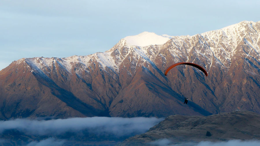 Person paragliding against rocky mountain during winter