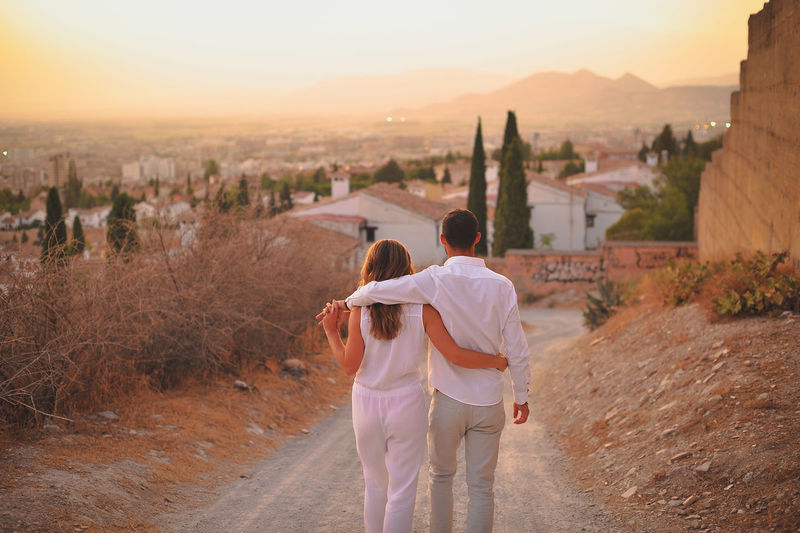 Rear view of young couple on dirt road in city at sunset