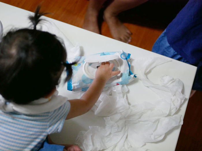 Rear view of girl pulling tissue paper while sitting on table