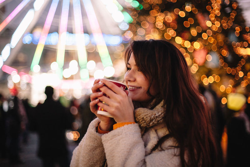 Portrait of smiling woman standing in illuminated park during winter