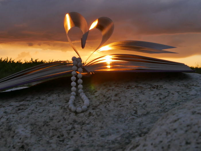 Book pages with beads making heart shape on rock during sunset