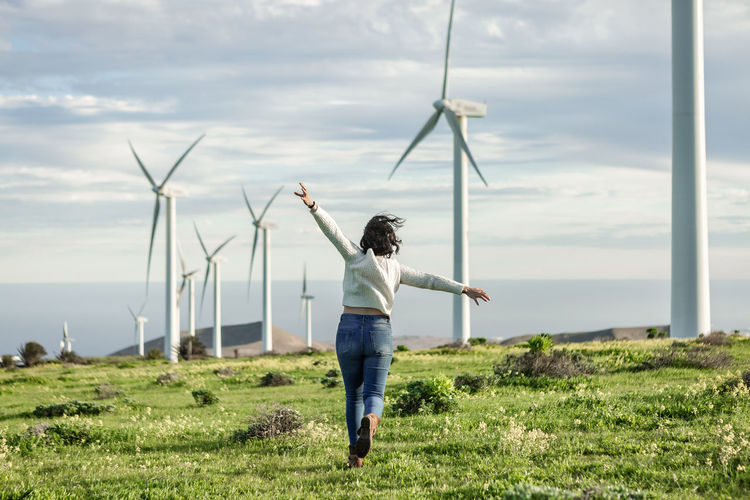 Rear view of woman running against wind turbines