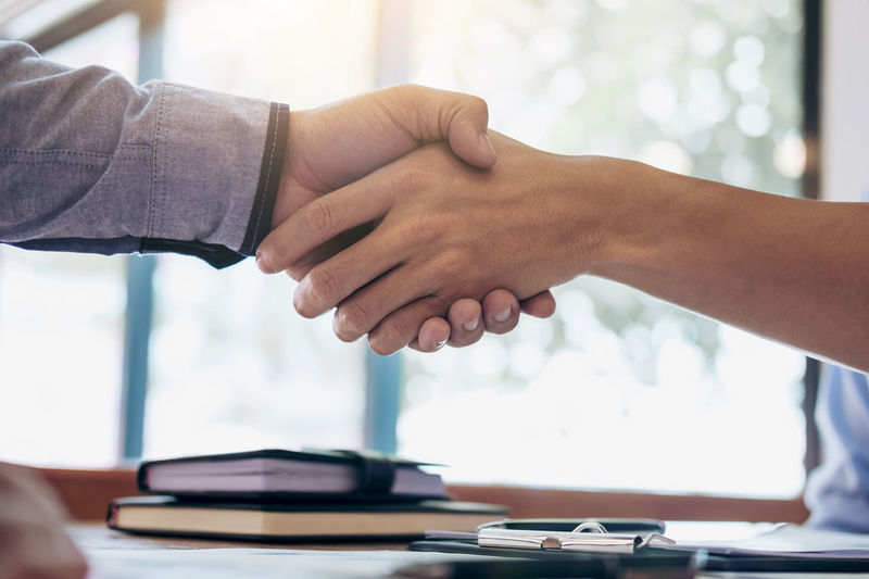 Midsection Of Businessman Handshaking With Colleague Over Office Desk