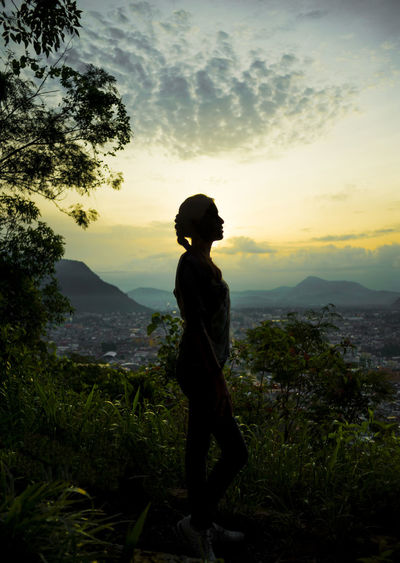 Silhouette teenage girl standing on mountain against sky during sunset
