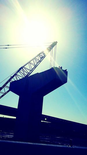 Bridge Birds Sun Ray Shining Bright Silhouette Contrast Construction Site Crane Blue Turquoise, Pale Yellow. The birds are having a spiritual experience.