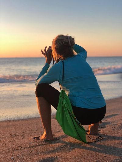 Woman crouching at beach against sky during sunset