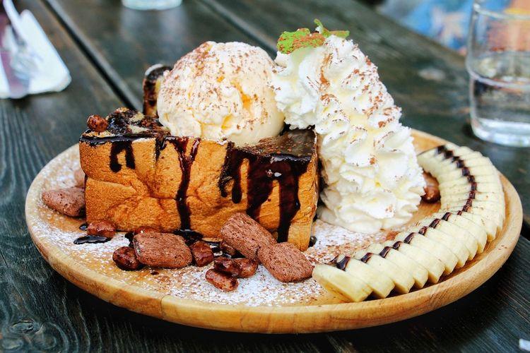 Honey toast dessert with whip cream and banana slices