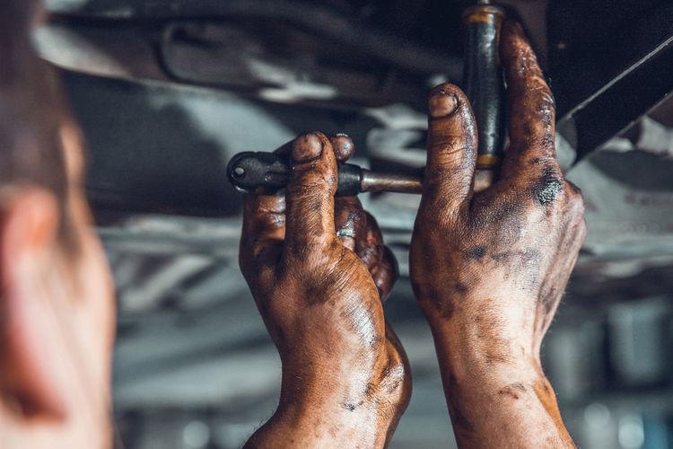 Cropped image of mechanic repairing vehicle