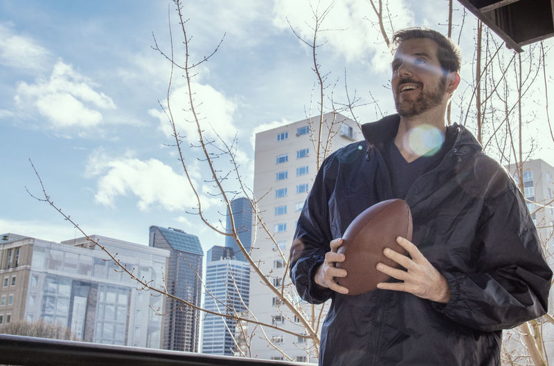 Smiling bearded man wearing jacket holding football with city skyline and blue sky. Weather Cold Temperature Jacket Football Bearded Handsome Real People Front View Standing Men Sky One Person Architecture Mid Adult Lifestyles Waist Up Outdoors Skyscraper Day Nature Grip Sports Fans Teamwork