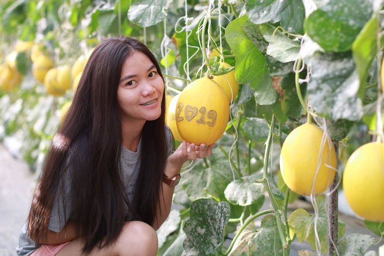 Portrait of smiling young woman holding fruit with numbers