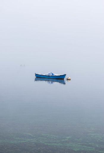 solitary boat in the lake on a foggy morning Foggy Weather Boat Boat In Lake Boat In Fog Boat In Water Day Focus On Foreground Foggy Foggy Landscape Foggy Morning Lake Lake View Nature Nautical Vessel No People Outdoors Transportation Water