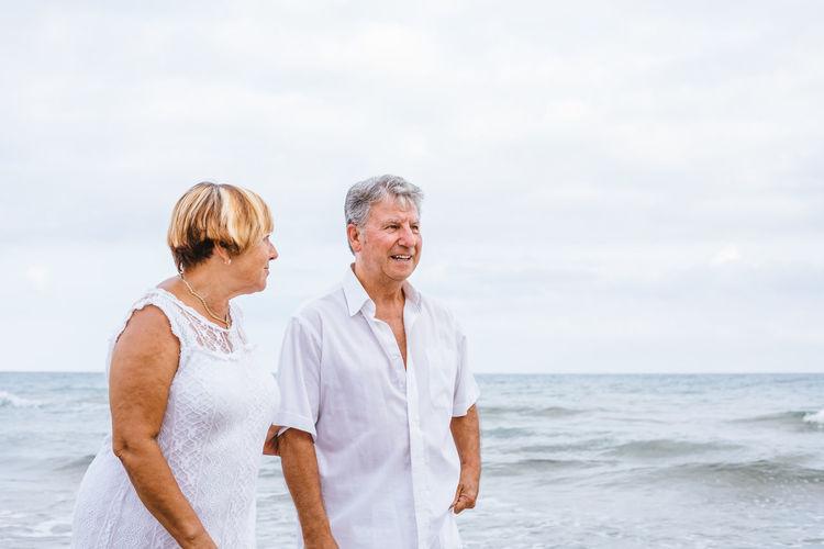 Romantic Senior Couple Standing At Beach Against Sky