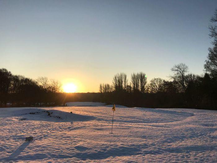 Scenic view of snow covered field against clear sky during sunset