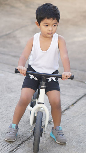 Boy riding bicycle on footpath