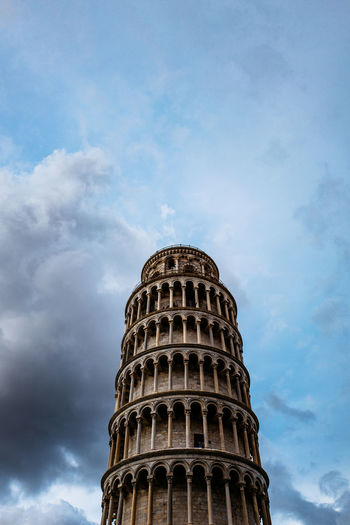 Low Angle View Of Leaning Tower Of Pisa Against Cloudy Sky