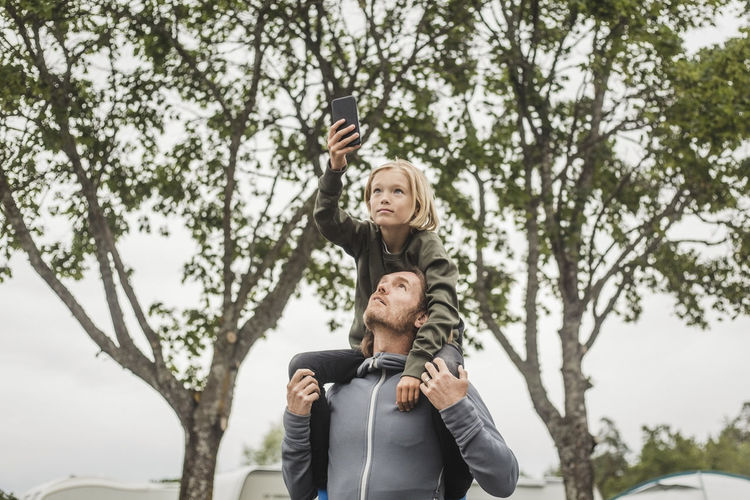 Portrait of smiling young woman using phone while standing on tree