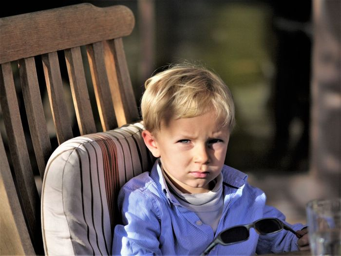 Portrait of boy sitting on chair