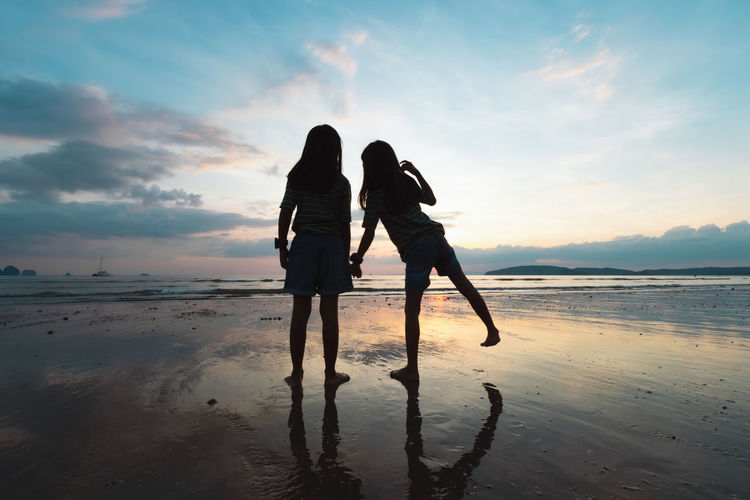 Silhouette girls holding hand standing on beach against sky