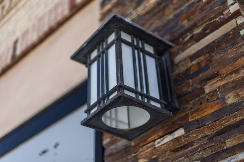 Lamp on the building wall Architecture Brick Wall Building Building Exterior Building Wall Built Structure Close-up Day Focus On Foreground Lamp Light Low Angle View No People Outdoors Shaded Shallow Depth Of Field Stone Wall Wall