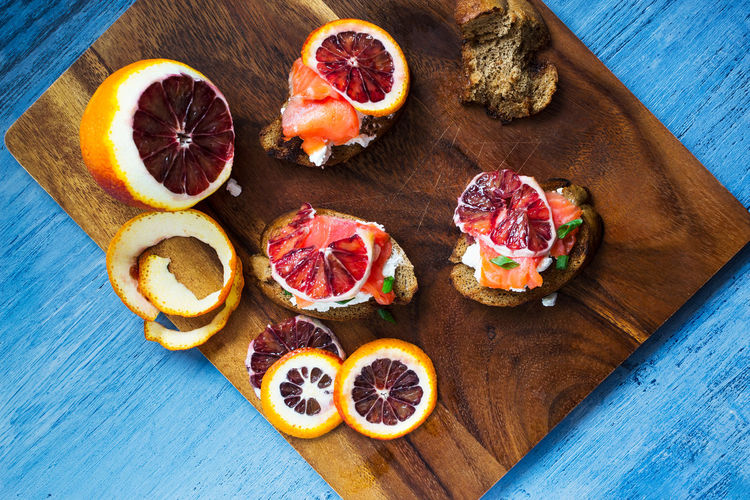 Blood Orange Blue Bruscetta Citrus Fruit Cutting Board Directly Above Food Food And Drink Freshness Fruit Healthy Eating High Angle View Indoors  No People Orange - Fruit Orange Color Salmon Sandwich Sandwich Time SLICE Snack Table Vibrant Blue Wood - Material The Foodie - 2019 EyeEm Awards