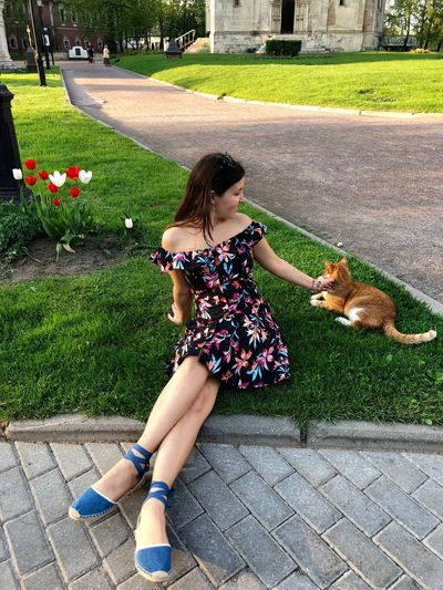 Woman Petting Cat While Sitting At Park