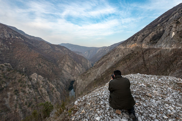 Man photographing mountains with camera against sky