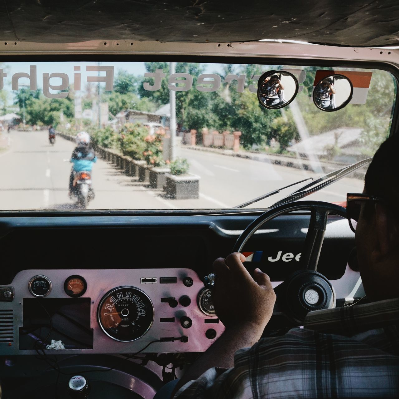 car, transportation, vehicle interior, land vehicle, mode of transport, car interior, real people, dashboard, steering wheel, windshield, human hand, men, day, windscreen, one person, human body part, speedometer, close-up, outdoors, people