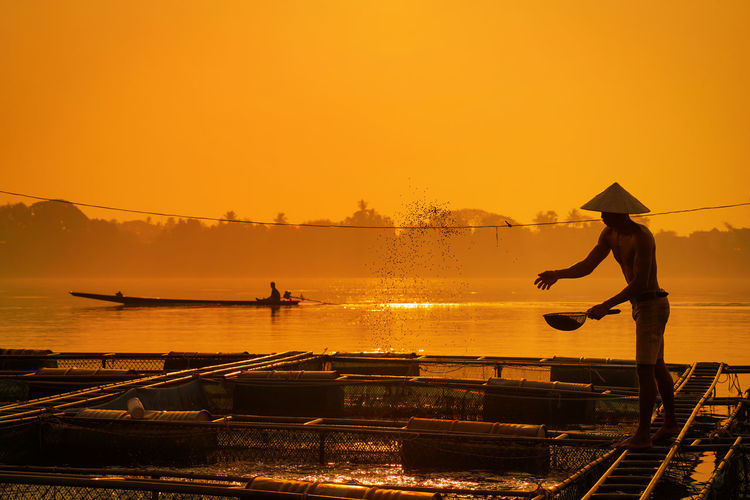 Fisherman feeds the fish in a commercial farm in Mekong river. Farmers feeding fish in cages, Mekong River. The Tilapia for feeding fish in northeast of Thailand. Sunset Water Sky Orange Color Real People One Person Nature Transportation Nautical Vessel Silhouette Lifestyles Beauty In Nature Full Length Occupation Standing Mode Of Transportation Hat Men Sun Outdoors Fisherman