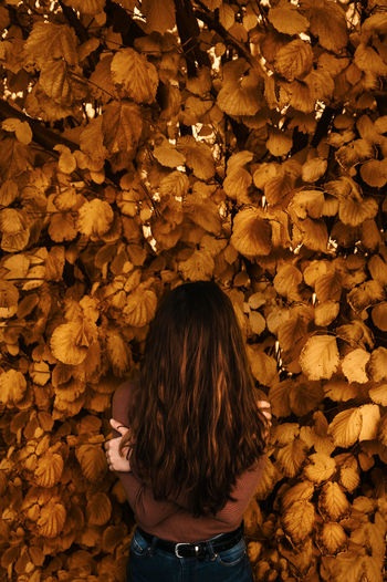 Woman Standing Amidst Leaves During Autumn