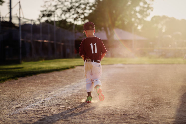 Rear view of boy walking on baseball field