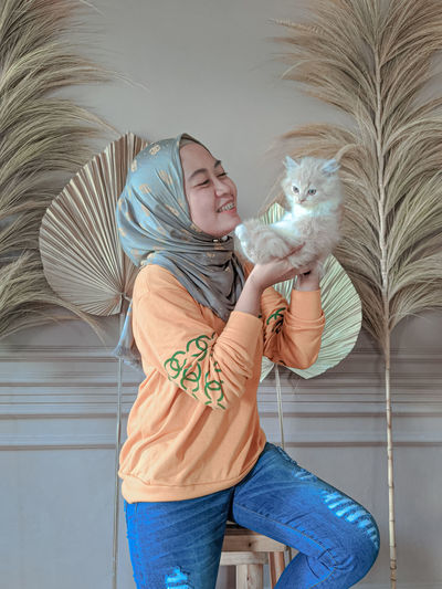 Full length of woman holding cat