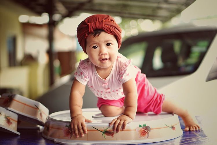 Portrait of cute baby girl on table