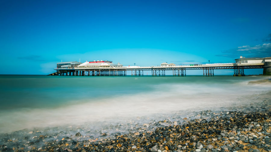 Pier on beach against blue sky