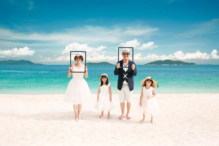 Portrait of happy asian family at sandy beach in summer vacation . Beach Beauty In Nature Cloud - Sky Day Dog Front View Horizon Over Water Leisure Activity Looking At Camera Mammal Men Nature Outdoors Portrait Real People Sand Sea Sky Standing Togetherness Vacations Wedding Wedding Dress Young Adult Young Men