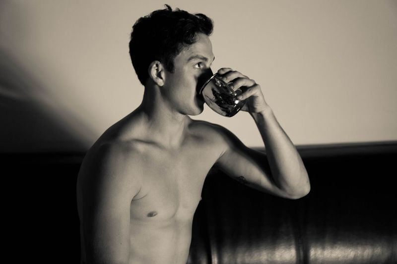 Midsection of shirtless man drinking water