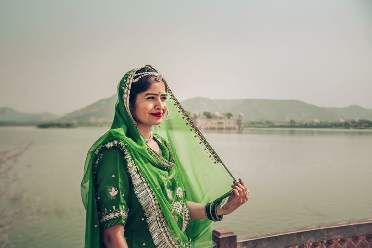 Portrait of beautiful woman standing by lake against sky