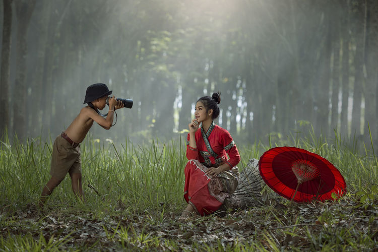 Junior photography shoot with model wearing red dress moment in natural Children Happiness Junior High Kids Playing Red Thailand Photos Adult Asian Food Day Feel Forest Full Length Grass Laos Nature One Person Outdoors People Photographer Portrait Real People Water Woemen Women Young Adult