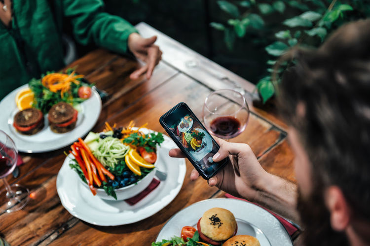 Man Photographing Food In A Restaurant Photographing Food Dinner Photographing Smart Phone Vegetarian Food Healthy Table Vegetable Colorful Hand Beautiful Lifestyle Delicious Lunch Plate Restaurant Health Vegan Vitamin Green Food And Drink Holding Male Hand Two People
