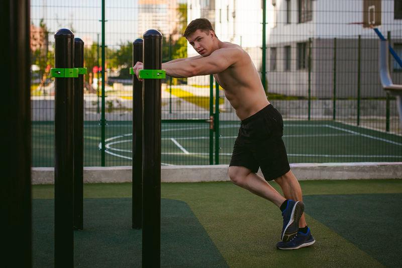 Muscular man exercising at park