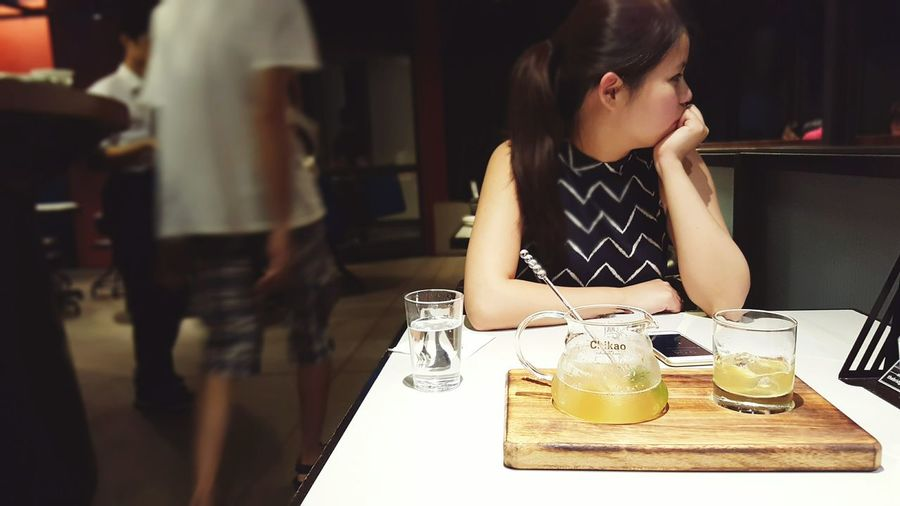 Young Woman With Cocktail At Table In Restaurant
