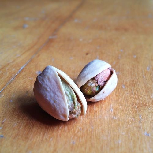 Two Pistachio Nuts On Wood