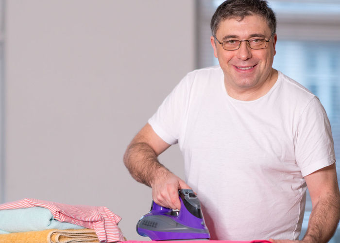 Portrait Of Smiling Man Ironing Cloth At Home