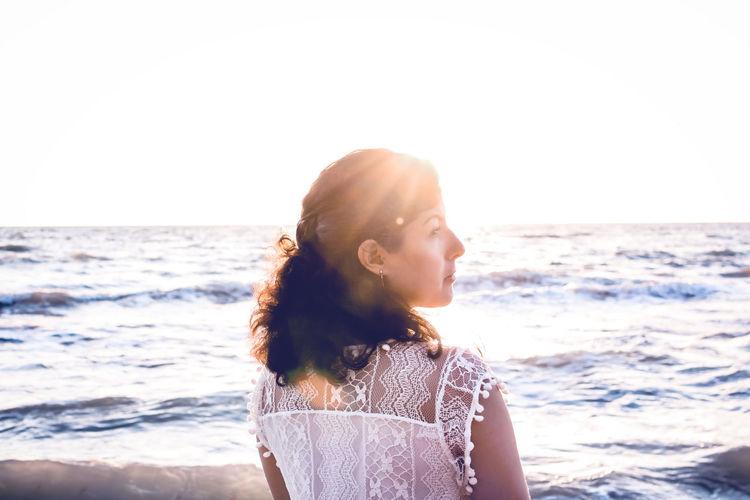 Woman at beach against clear sky