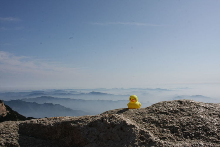 Yellow toy on rock against sky