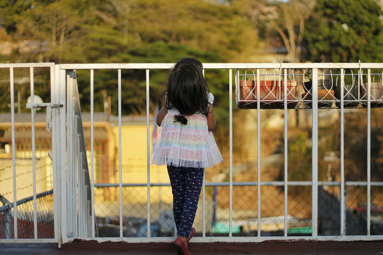 Rear View Of Girl Standing By Railing Against Trees