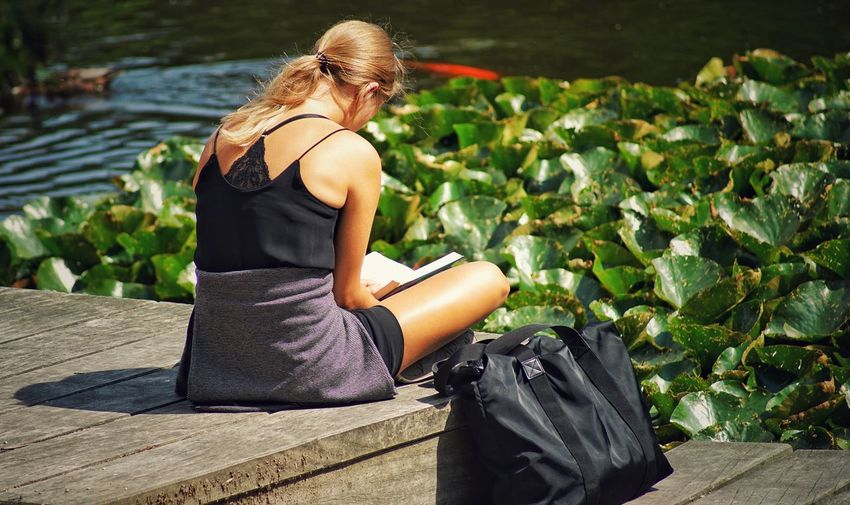 Woman reading book while sitting on boardwalk