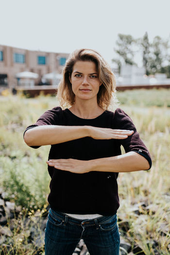 Portrait of woman gesturing equal sign while standing on field