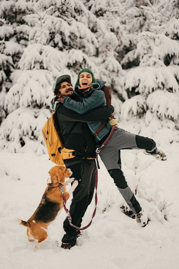 View of a couple and a dog on snow covered landscape during winter